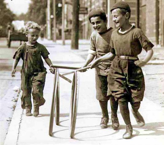 Children playing with hoops and sticks.