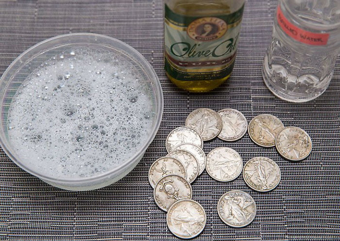 Soaking old coin in vinegar to clean them
